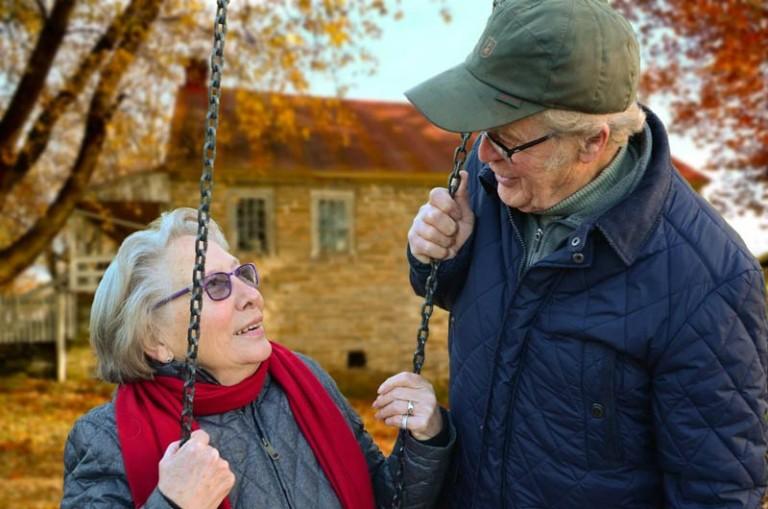 Dziadkowie na huśtawce omawiają wideofon dla wioski emerytalnej